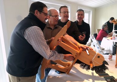 Team assembling a child's rocking chair