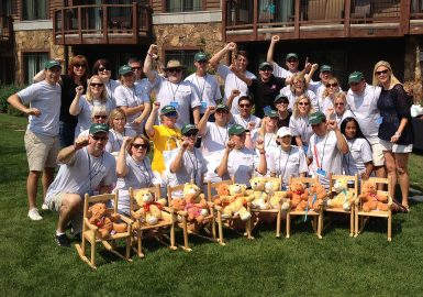 Teams cheering with their donations of rocking chairs and stuffed bears