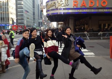 Team doing a Rockette leg kick in the air in front of Radio City Music Hall in NYC