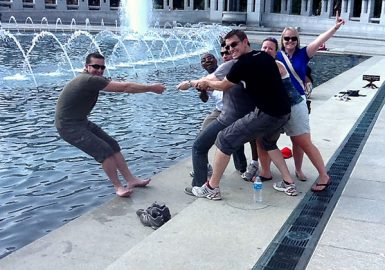 Picture of team doing a trust lean exercise with rope on the edge of a fountain pool