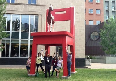 Participants pose standing under a giant chair statue