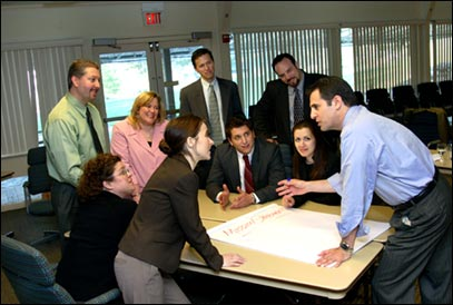 Two business partners engaging each standing around a table talking while others sit and watch