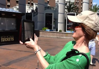 Woman filming trailer with iPad facing towards her