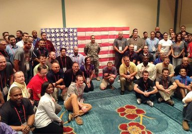 Teams with completed Operation Military Care packages assembled in the shape of the American flag