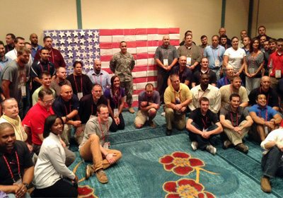 Picture of participants sitting in front of a completed Operation Military Care flag