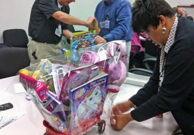 Female participant putting the finishing touches on her completed Holiday Toy Donation wagon
