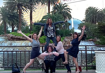 Ladies doing a cheer pose standing in front of a pond