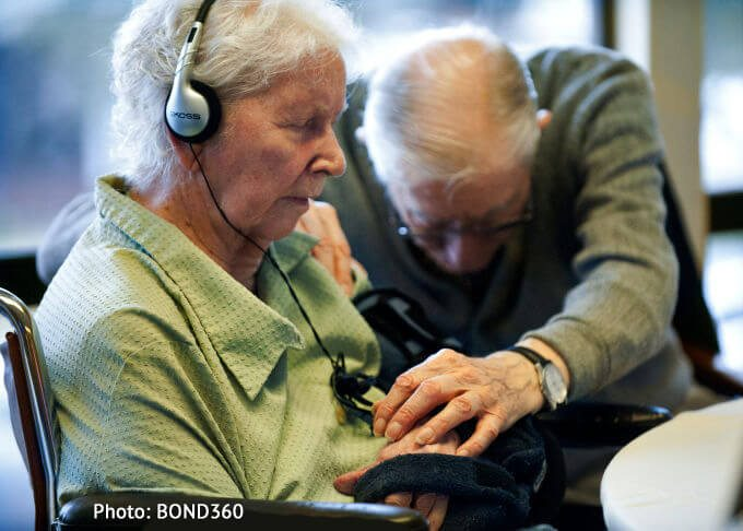 Patient sitting with her eyes closed listening to music while t