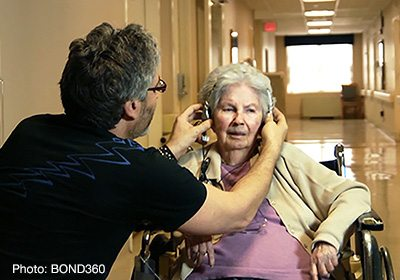 Elderly woman sitting in a wheelchair getting headphones put on by a gentlemen