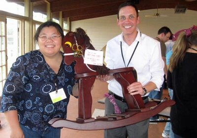 Two teammates hold up completed brown rocking horse with personalized note attached