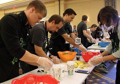 teammates with gloves on their hands prepping food at their table