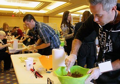 Participants with gloves on stirring a bowl of beans at his food-prep table