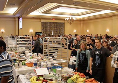 Large group of participants stand behind tables full of food