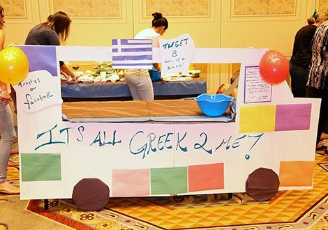 """Picture of a cardboard Greek cut out of a food truck with the slogan """"It's all Greek 2 Me!"""""""