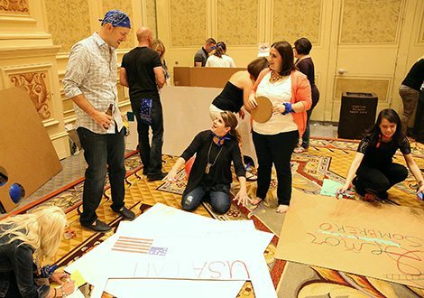 Participants sitting on the in a hotel meeting room floor working on designing their cardboard signs