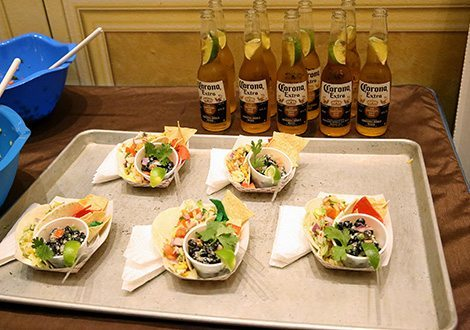 Picture of finished neatly organized dishes on a silver tray on a prep-table with Corona Extra's lined up on the back of the table