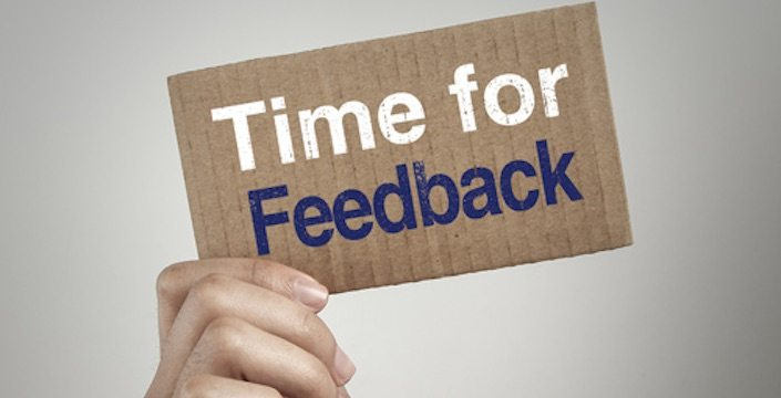 Hand holding up cardboard sign that says: Time for Feedback