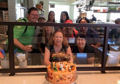 Foodie SmartHunt® team poses behind a fancy cake