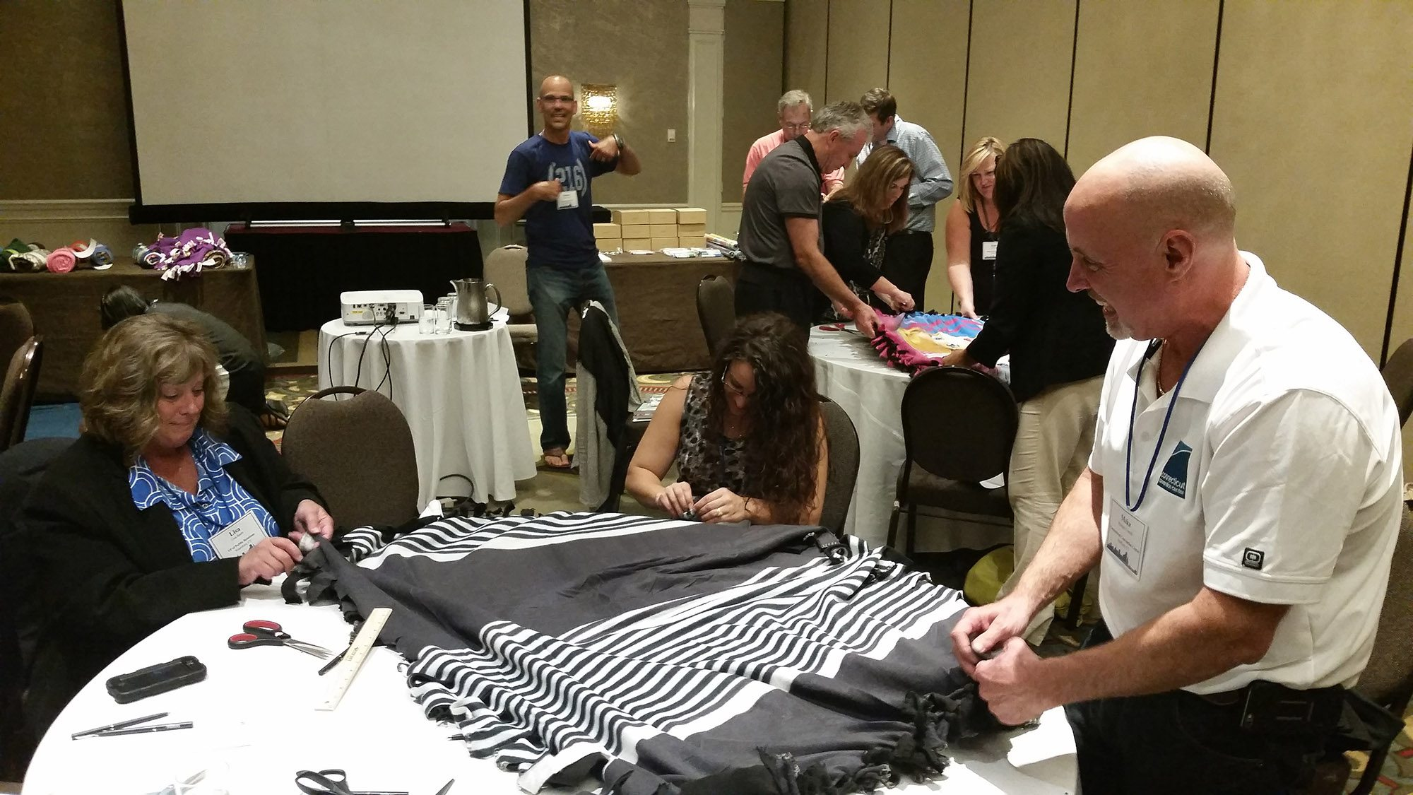 Teammates crafting their blanket on a table in a hotel conference room
