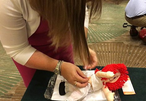 Teammate tinkering with a Raggedy Ann Doll on a table inside during Wagon Build Donation™ program