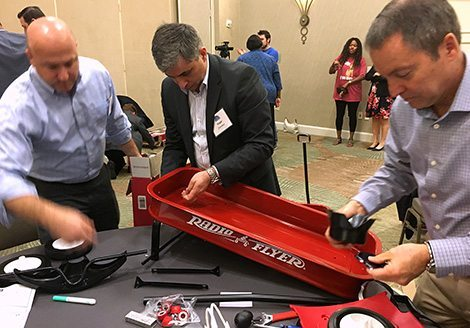 Team assembling a radio flyer inside on a table during Wagon Build Donation™ program