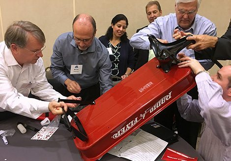 Team assembling radio flyer on a table inside during Wagon Build Donation™ program