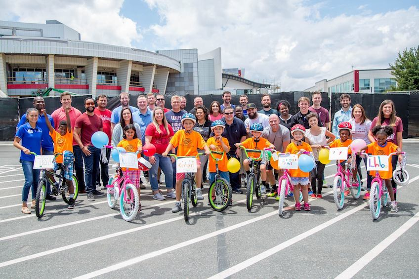 Team with their completed Boys and Girls Club Bike Donation and the children that received themn