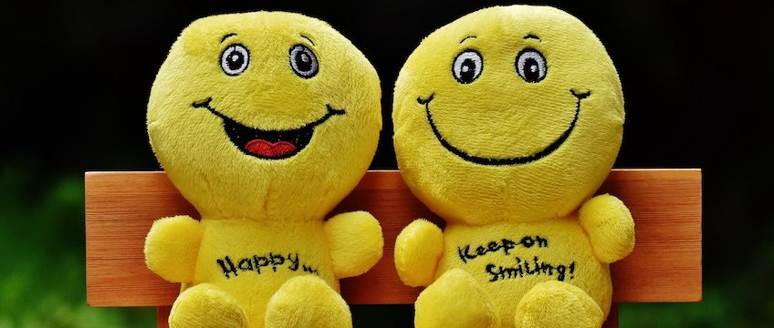 Smiling Yellow Stuffed Animals Sitting on a Bench