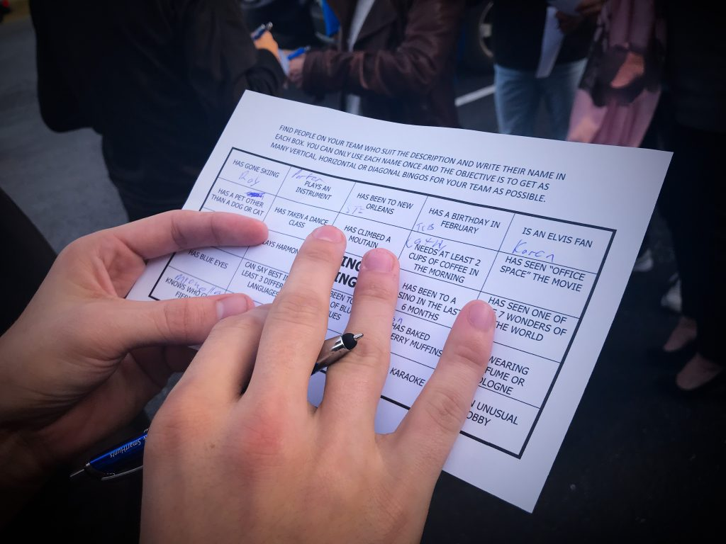 two hands holding a bingo card that he's filling out