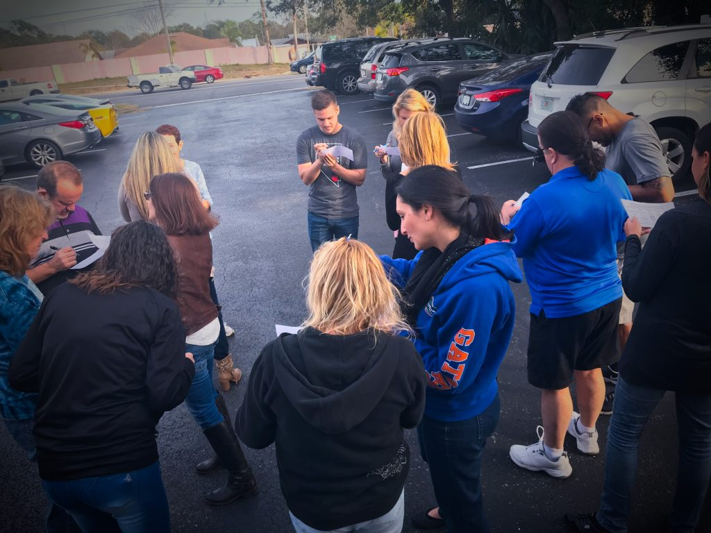 group of people forming a circle in a parking lot filling out bingo cards