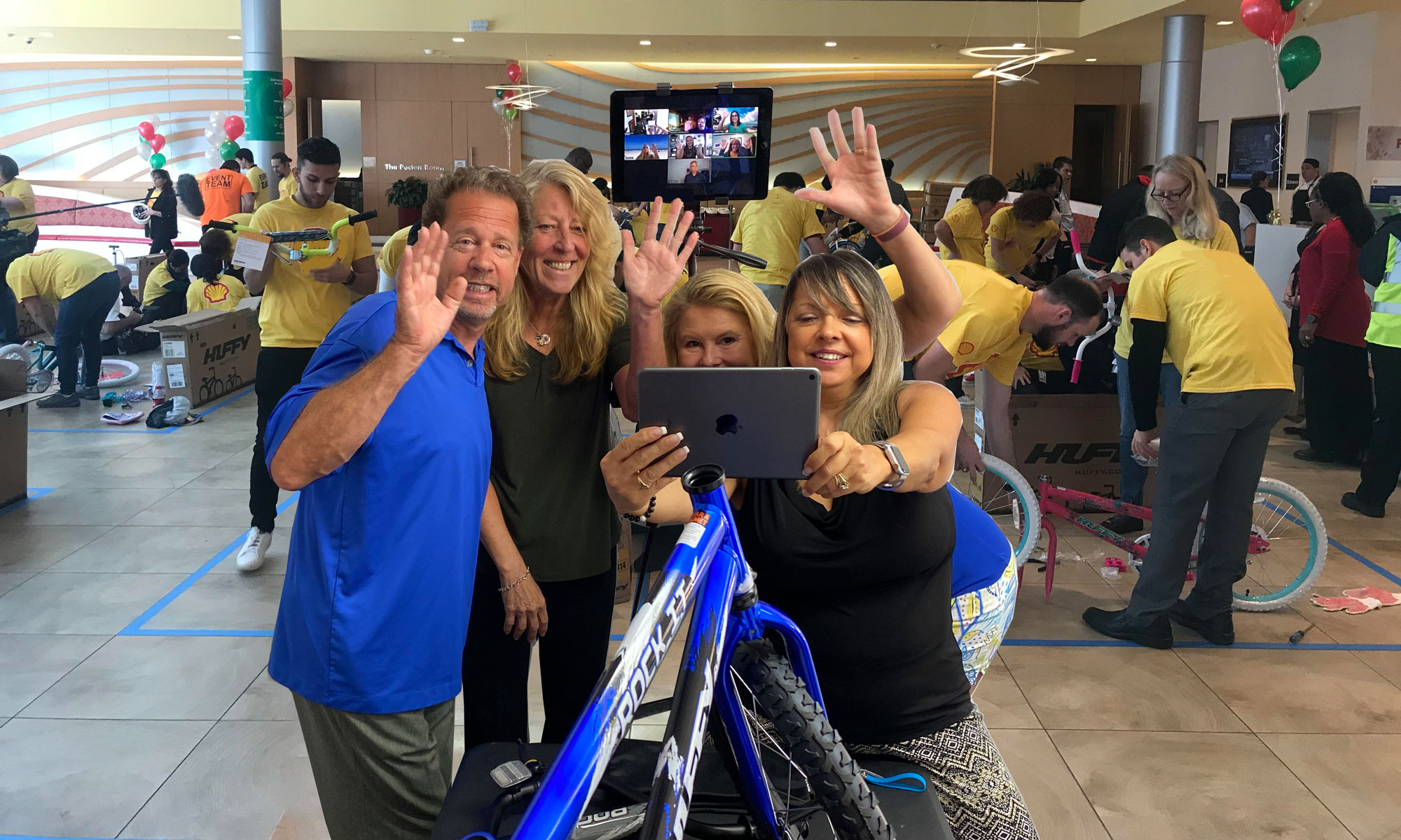 Above: At a Hybrid Bike Build Donation program, an In-Person team is taking a selfie with their remote teammates who are on the iPad behind them! Cameras around the room are broadcasting the event to all remote participants, while they interact with their in-house team using their own mobile devices to gain points, solve clues, answer trivia, and competing in fun, team challenges.
